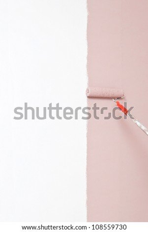 Painting the wall pink with a roller - stock photo
