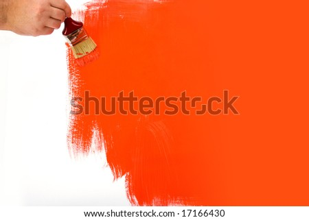 Painting the wall red with a paint brush - stock photo