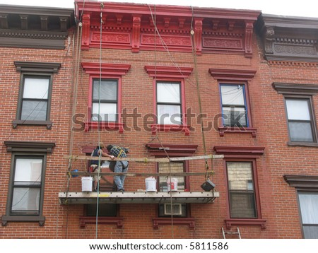 Painting the Windows of a Townhouse - stock photo