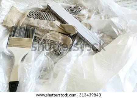 Painting Tools for home renovation with some plastic foil for covering.  - stock photo