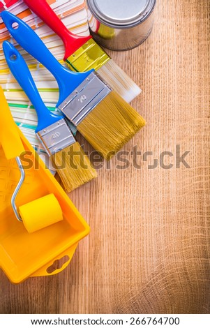 painting tools paint brush roller tray can color palette on wooden board  - stock photo