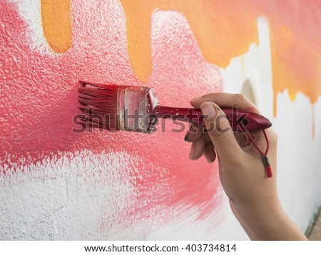 Painting Walls,man holding a paintbrush with a partly finished blank red and white painted wall. Space for copy,hand worker holding brush painting on wall ,Workers painted walls,selective focus. - stock photo