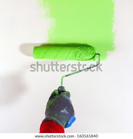 Painting white wall with paint roller - stock photo