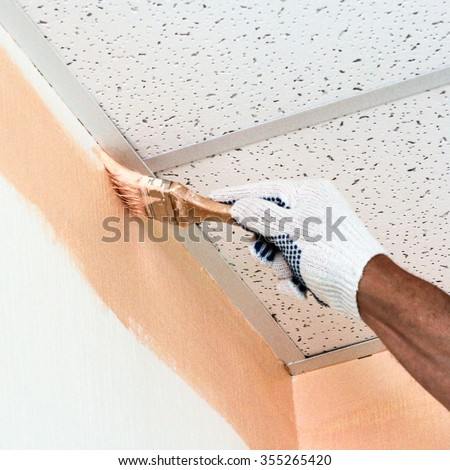 Painting with a brush near the ceiling.