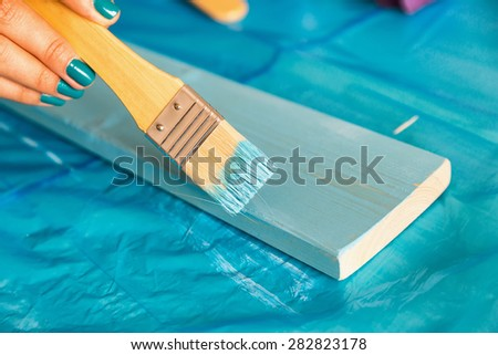 Painting wood at home with a brush. - stock photo