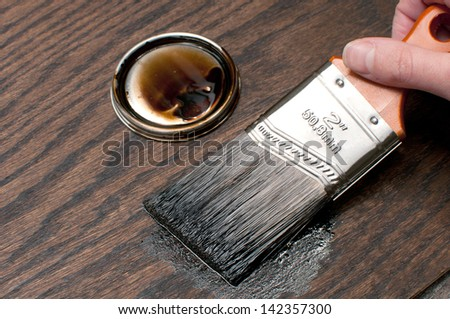 Painting wood in darker brown color with brush - stock photo