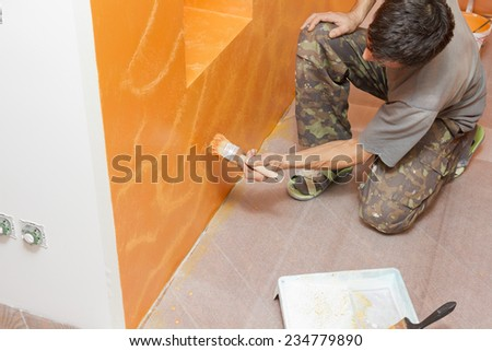 Painting worker inflicts structural paint on the wall. - stock photo