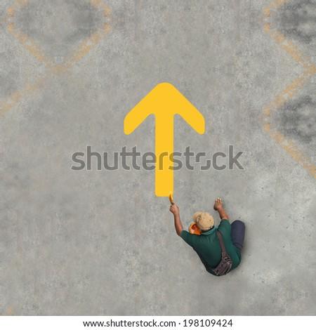 Painting yellow arrow on the floor - stock photo