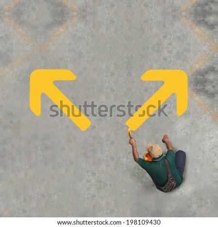 Painting yellow arrows on the floor - stock photo
