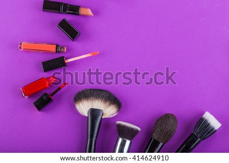 Paints, brushes and other tools make-up on a purple background - stock photo