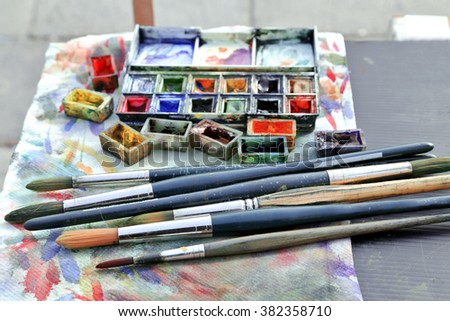 Paints, brushes water-color background