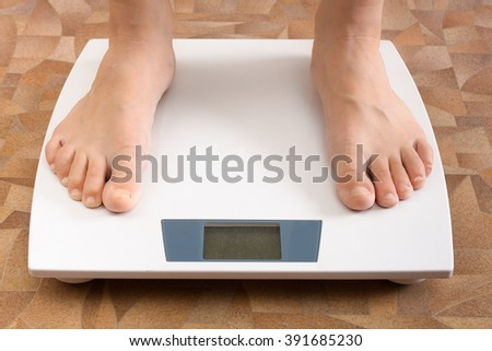 pair feet standing on the scale - stock photo