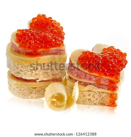 Pair heart shape of sandwich with red caviar isolated on white - stock photo