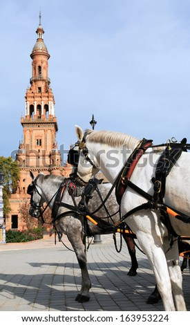 "Pair horses with coach against ancient belfry. ""Plaza de Espana"", Seville, Spain - stock photo"