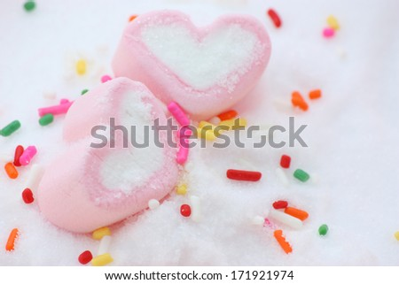 pair if pink heart shape marshmallows around by rainbow candy on snow
