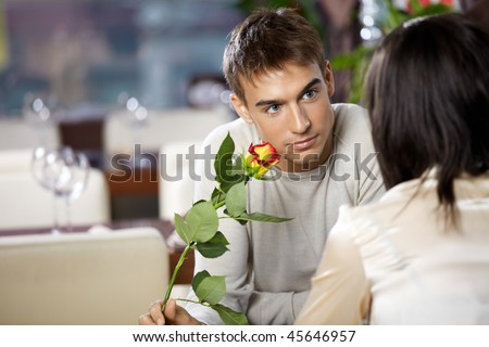 Pair in cafe - man gives to woman a flower - stock photo