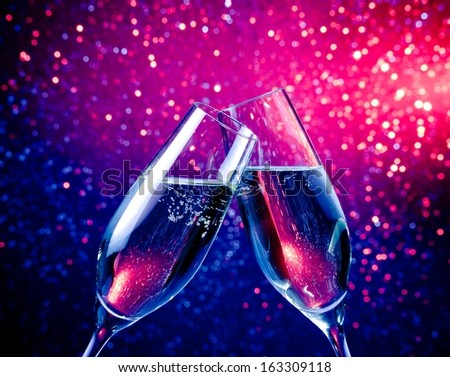 pair of a champagne flutes with bubbles make cheers on blue tint light bokeh background - stock photo