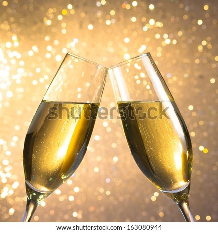 pair of a champagne flutes with golden bubbles make cheers on light bokeh background - stock photo