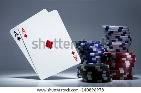 Pair of Aces playing cards balanced on white next to some poker chips. Gambling concept - stock photo