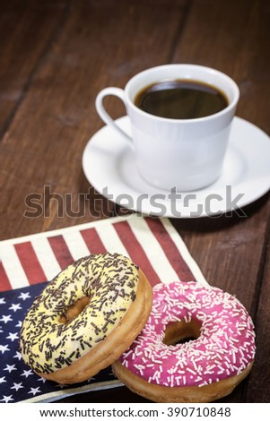 Pair of American donuts are lying on a napkin  with the design of the American flag. Cup of coffee is in the background. Photo is designed as a vintage with dark edges. - stock photo