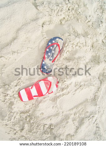 Pair of  American flag flip flops on white sand beach. - stock photo