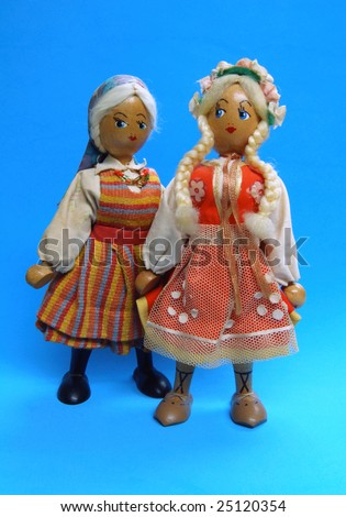 Pair of antique Polish girl dolls on blue background