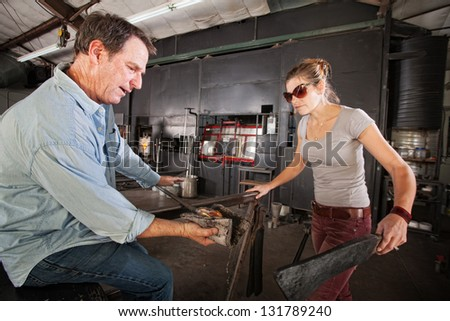 Pair of artisans working at a glass company with tools - stock photo