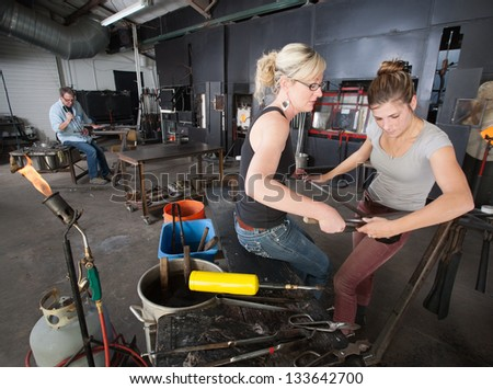Pair of artisans working with tools in glass art workshop