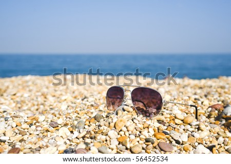 Pair Of Aviator Sunglasses Lying On The Beach - stock photo