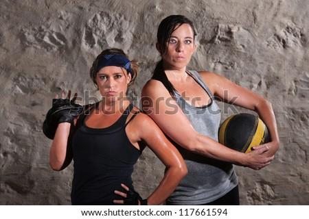 Pair of beautiful women holding boot camp training equipment - stock photo