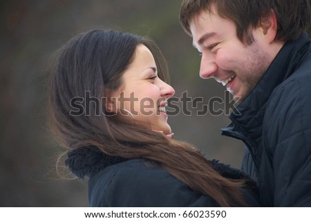 pair of beautiful young people hugging in the park in warm clothes