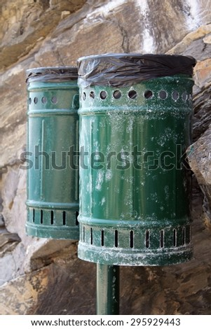 Pair of bins for waste, metal, green color. In the background the rock.