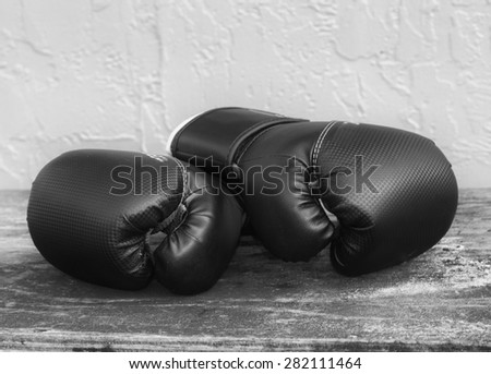 Pair of black boxing gloves on an old wood grained table against a textured wall in black and white - stock photo