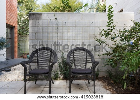 Pair of black cane outdoor chairs in modern paved Australian apartment courtyard - stock photo