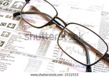 Pair of black frame spectacles on newspaper financial page