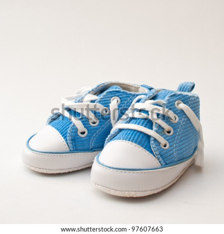 Pair of blue and white baby sneakers over gray background