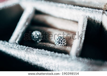 Pair of blue diamond crystal earrings in luxurt storage box - beautiful jewelry - tilt-shift lens used to outline the object and to emphasize the attention on them - stock photo
