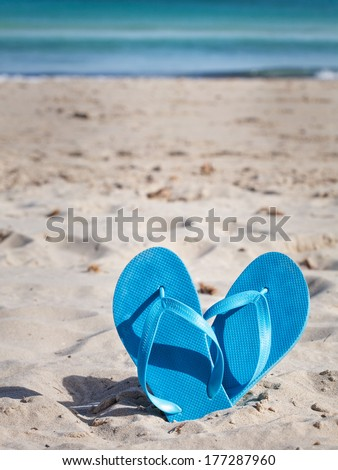 Pair of blue flip flops on sand beach - stock photo