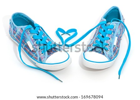 Pair of blue sneakers with laces isolated on white - stock photo