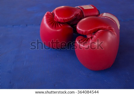 Pair of boxing gloves hanging in a rustic blue Background - stock photo