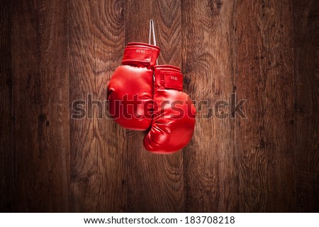 Pair of boxing gloves hanging on a wooden wall - stock photo