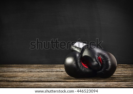 Pair of boxing gloves on a vintage wooden desk with chalkboard background. Concept image, the idea of brutal competition. - stock photo
