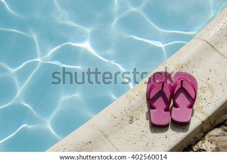 Pair of bright summer sandals at edge of pool - stock photo