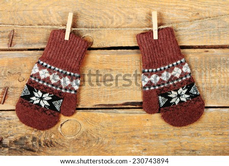 Pair of brown mitten with ethnic ornament on old wooden background - stock photo