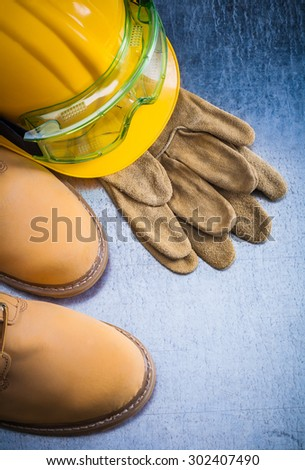 Pair of brown safety lace shoes leather gloves hard hat and working goggles on scratched metallic background construction concept. - stock photo