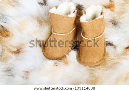 Pair of brown winter boots on fox fur background - stock photo