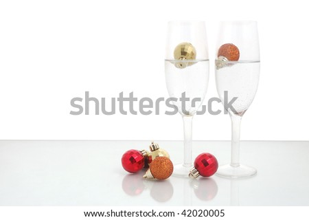 Pair of champagne flutes and christmas balls against a white background - stock photo
