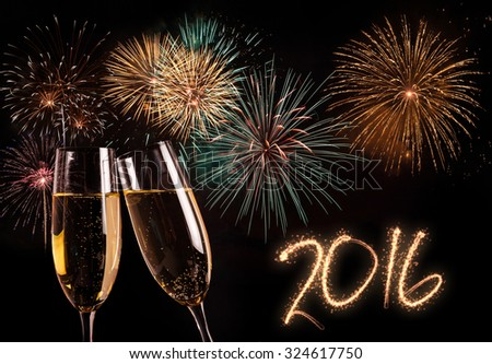 Pair of champagne flutes and fireworks in the background. New year 2016 concept - stock photo
