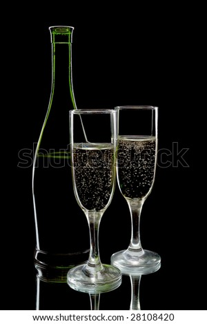 Pair of champagne flutes and wine bottle against a black background - stock photo