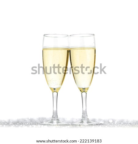 Pair of champagne flutes on shiny glitter background